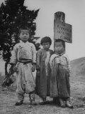 Children Standing in Front of Boundary Zone Sign Written in Russian  English  and Korean