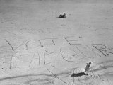 "Girl Standing by the Words ""Vote Labour"" Written in the Sand"