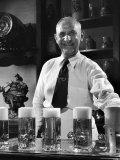 Bartender Smiling as He Serves Large Glasses of Beer