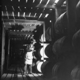Employee in Warehouse of Jack Daniels Distillery Checking For Leaks in the Barrels