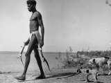 Australian Aborigine Man Bringing Back Two Monitor Lizards Known as Goannas to His Clan