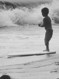 Little Boy Standing on a Surf Board Staring at the Water