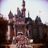 Crowds Walking Through Gate of Sleeping Beauty's Castle at Walt Disney's Theme Park  Disneyland