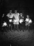 Children Holding Sparklers on a Beach