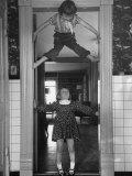 """Denise Bruene Climbing Kitchen Door in Bare Feet  Her Hobby  Jan Bruene Says """"Don't Fall on Me"""""""