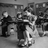 Cute Little Girl Busily at Work  Sitting in a Desk Chair in a Schoolroom  Other Pupils at Work Too