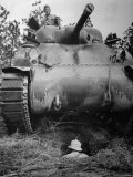 Oncoming View of Tank About to Pass over Foxhole in Which a Soldier is Crouched Down