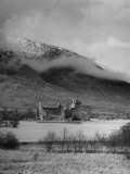 Old Scottish Castle Standing on a River Peninsula  with Mountain Rising in Background