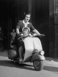 Mother and Baby Riding a Vespa Scooter