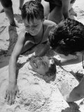 Settlement House Children Burying Boy under Sand at the Beach