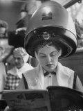 Woman Sitting under Hair Dryer Reading a Magazine