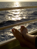 Woman's Feet Resting on the Railing of a Cruise Ship at Sunset