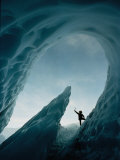 A Climber Raises His Ax in Triumph Near the Opening of an Ice Cave