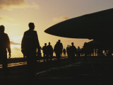 Silhouetted Military Personnel on an Aircraft Carrier at Twilight