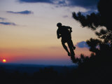 Silhouette of Mountain Biker in the Air against Sunset Sky