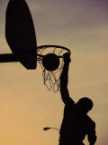 Silhouette of a Man Slam Dunking a Basketball