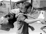 A South Vietnamese Father Carries His Son and a Bag of Household Possessions
