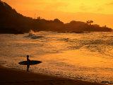 Surfer Standing at Waimea Bay at Sunset  Waimea  USA