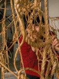 Eva Hesse Peering Through Her Sculpture of Rubber Dipped String and Rope Aluminium par Henry Groskinsky