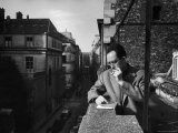 French Writer Albert Camus Smoking Cigarette on Balcony Outside His Publishing Firm Office