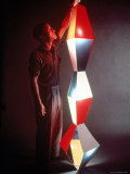 Japanese American Sculptor Isamu Noguchi Adjusting a Light Sculpture He Designed