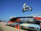Daredevil Motorcyclist Evil Knievel in Mid Jump over a Row of Cars
