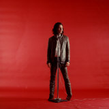 Rock Star Jim Morrison of the Doors Standing Behind Microphone Alone Against a Red Backdrop
