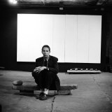 Robert Rauschenberg Sitting on One of His Sculptures in His Studio