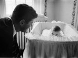 Sen Jack Kennedy Admiring Baby Caroline as She Lies in Her Crib in Nursery at Georgetown Home