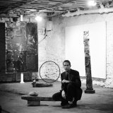 Robert Rauschenberg Sitting on His Sculpture in Studio  Among Other Paintings and Sculptures