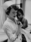 Nurse Holding African American Girl in Her Arms  Examining Her Finger