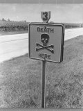 """Skull and Crossbones Surrounded by the Words """"Death Here"""" marking fatal car accident"""