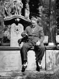 Publisher William Randolph Hearst Sr  Petting Dachshund Gandhi While Sitting on Edge of Fountain