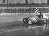 Track Record Holder Ted Tappett Circling Track With Checkered Flag After Winning