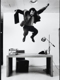 Architect and Designer Frank Gehry Jumping on a Desk in His Line of Cardboard Furniture