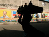 A Boy Carrying Bottles on His Head Passes by a Wall with Pictures of Haitian President Renel Preval
