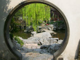 Zig Zag Stone Bridge and Willow Trees Through Moon Gate  Chinese garden  China