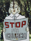A Rusting Metal Sign Advising People to Stop for Church