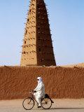 Robed Tuareg Man Cycling Past Minaret of Mud-Brick Grande Mosquee  Agadez  Niger