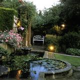 Garden Lighting Beside Italianate Pool & White Female Statue  Wrought Iron Bench