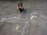 A Young Girl Admires a Drawing That She Did with Sidewalk Chalk