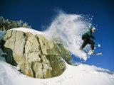 Snowboarder Jumping off a Big Rock