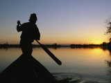 A Silhouetted Burmese Man in a Canoe at Sunset