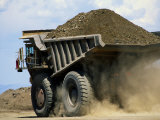 A Dump Truck Carrying Gravel Kicks up a Cloud of Dust