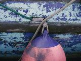 A Colorful Buoy Hangs from Ropes off the Side of a Boat