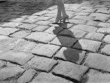 A Lady in High Heels Walks Along a Cobblestoned Street