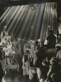 Rays of Sunlight Shine on Men and Boys in a Crowded Warehouse