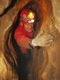 Man in Caving Gear in the Entrance to the Laundry Chute  a Narrow Corridor in the Rats Nest Cave