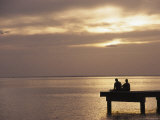 Two People Fishing on a Pier Looking Out at Sunset over the Pacific Ocean