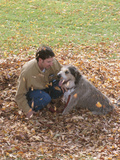 Man Playing with Dog in Autumn Leaves